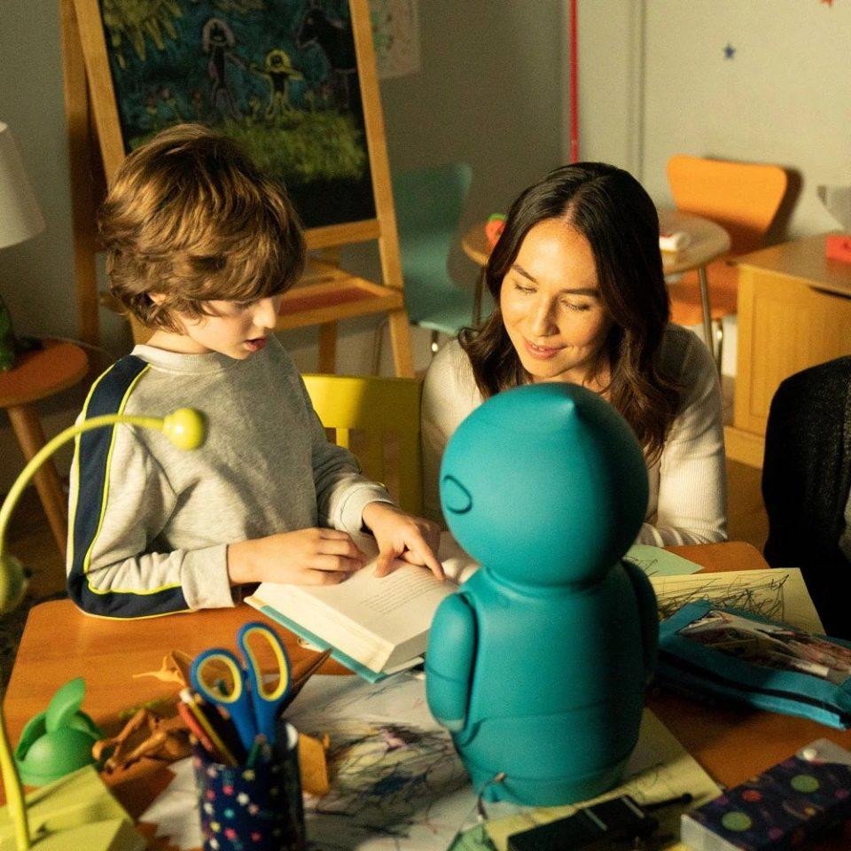 Un bambino legge un libro con Moxie e la sua mamma. Design a servizio dell'intelligenza artificiale per bambini